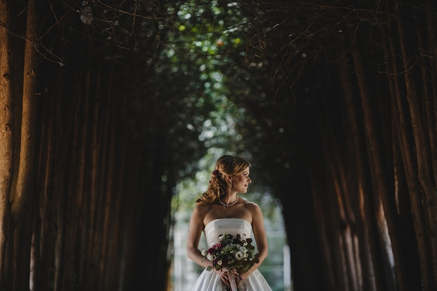 The beautiful bride with bouquet stands in the park
