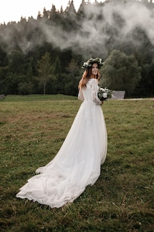 Beautiful bride with a bouquet and a wreath on her head looking at the camera. bride in a field in autumn.