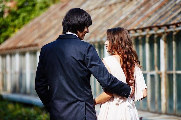 緑の葉の背景、結婚式の写真、美しいカップルで互いに近くに立っている巻き毛と花婿を持つ美しい花嫁。