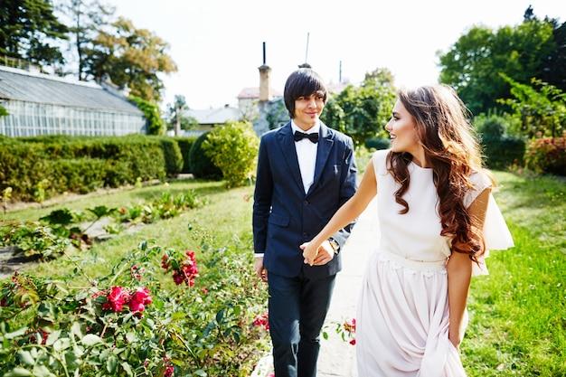 緑の葉の背景、結婚式の写真、結婚式の日、肖像画で互いに近くに立っている巻き毛と花婿を持つ美しい花嫁。