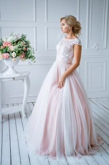 A beautiful bride with hair and makeup stands in a delicate pink wedding dress in a light decor with flowers