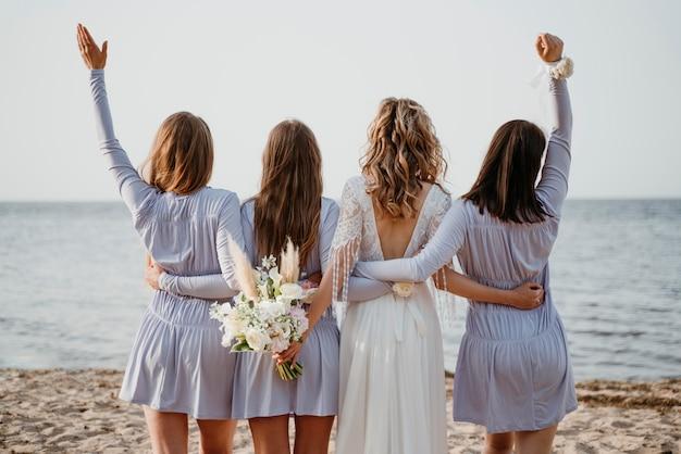 ビーチでの結婚式で彼女の花嫁介添人と美しい花嫁