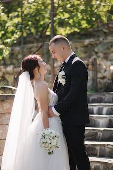 結婚式の日に外を歩いているハンサムな新郎と美しい花嫁。