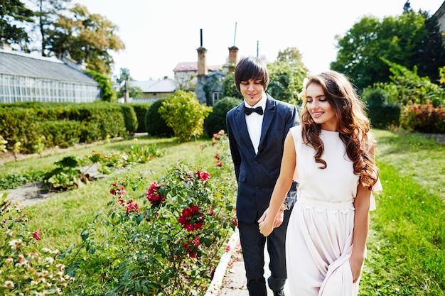 緑の背景、美しいカップル、結婚式の日に互いに近くに立っている長い巻き毛と花婿を持つ美しい花嫁。