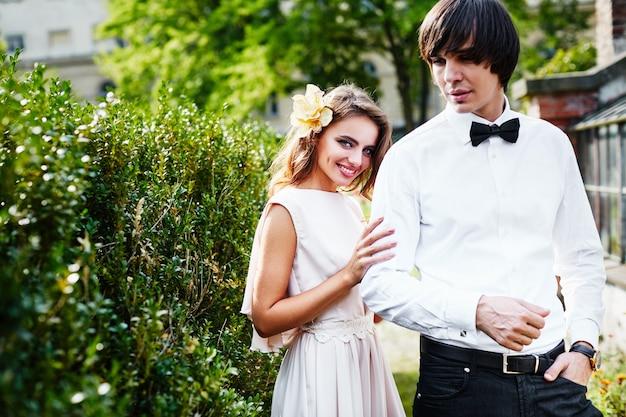 緑の葉の背景に、長い巻き毛と花婿が近くに立っている美しい花嫁、美しいカップル。
