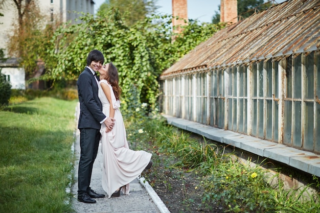 緑の葉の背景、結婚式の写真、美しいカップルで互いに近くに立っている長い巻き毛と花婿を持つ美しい花嫁。