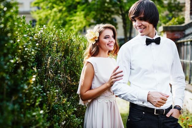 緑の葉の背景、結婚式の写真、結婚式の日、肖像画で互いに近くに立っている長い巻き毛と花婿を持つ美しい花嫁。