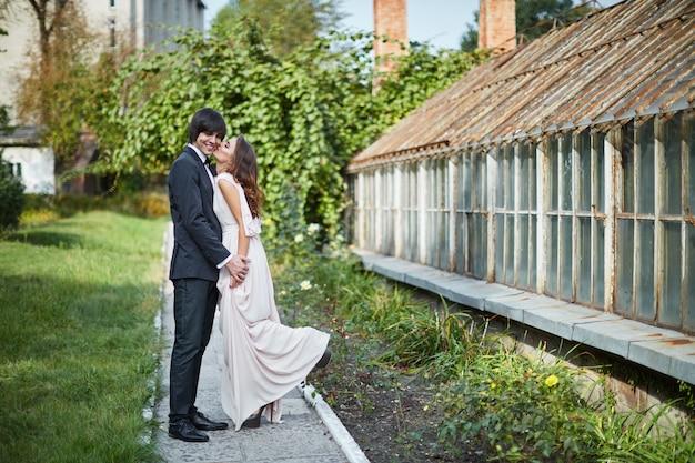 Красивая невеста с длинными вьющимися волосами и жених, стоя рядом друг с другом на зеленых листьях, свадебное фото, красивая пара.