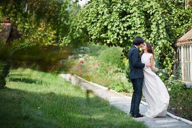 Красивая невеста с длинными вьющимися волосами и жених, стоя рядом друг с другом на зеленых листьях, свадебное фото, день свадьбы, портрет.