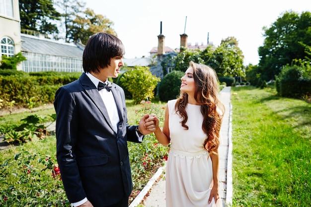 長い巻き毛と花婿が公園の背景で互いに近くに立っている美しい花嫁、美しいカップル、結婚式の日、肖像画を閉じます。