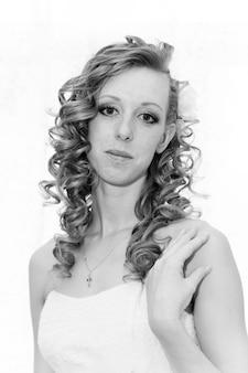 長い巻き毛の美しい花嫁。白黒写真