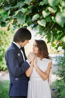 Beautiful bride with long curly hair and bridegroom standing close to each other at green leaves, wedding photo, beautiful couple,close up portrait.