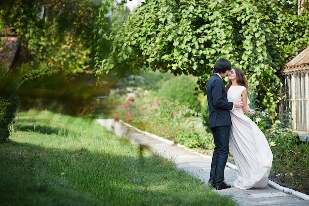 Beautiful bride with long curly hair and bridegroom standing close to each other at green leaves, wedding photo, wedding day, portrait.