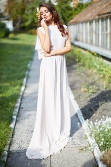Красивая невеста с длинными вьющимися волосами в свадебном платье, стоящем в парке, свадебное фото, портрет.
