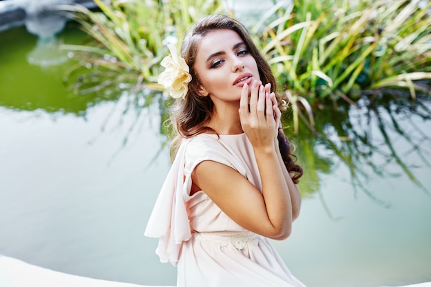 Beautiful bride with long curly hair in wedding dress sitting near fountain at park, wedding photo, portrait, close up.