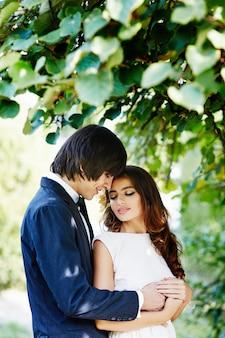 Красивая невеста с длинными волосами и жених, стоя близко друг к другу на зеленых листьях, свадебное фото, красивая пара, крупным планом.