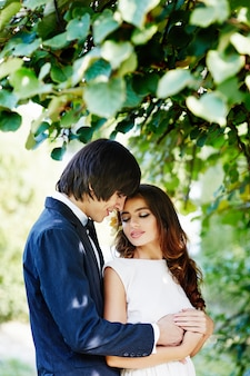 Beautiful bride with long  hair and bridegroom standing close to each other at green leaves, wedding photo, beautiful couple, close up.
