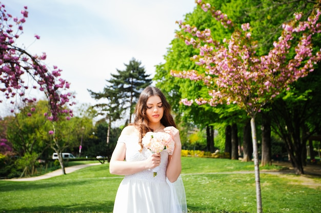Beautiful bride with wedding bouquet of lavender posing on the nature.