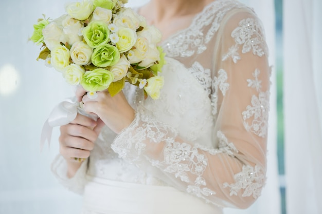 Beautiful bride with wedding flowers bouquet
