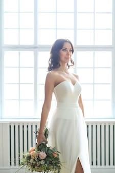 Donna bella sposa in abito da sposa elegante con bouquet di fiori