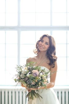Beautiful bride woman in elegant wedding dress with bouquet of flowers