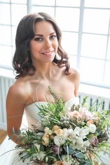 花の花束とエレガントなウェディングドレスの美しい花嫁の女性