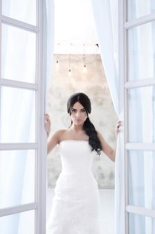 꽃의 꽃다발을 들고 웨딩 드레스에 아름 다운 신부 여자