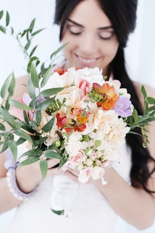 Beautiful bride woman in wedding dress holding a bouquet of flowers