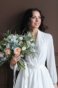 Beautiful bride woman in white robe with bouquet of flowers