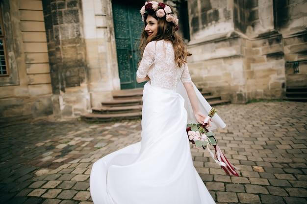 Beautiful bride in a wreath dancing in the street