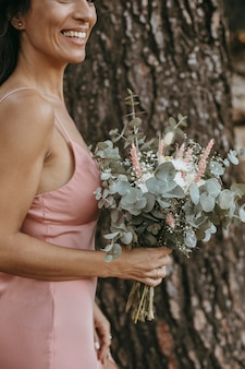 Beautiful bridesmaid holding a floral bouquet