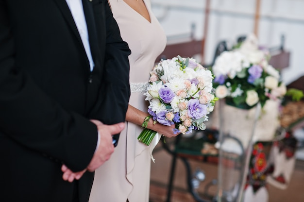 Beautiful bridesmaid holding a wedding bouquet in the church.