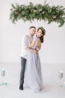 松の花輪とスタジオのハグでハンサムな花婿介添人と灰色のドレスで美しい花嫁介添人
