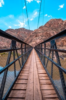 The beautiful bridge that crosses the colorado river at the end of the south kaibab trailhead trek. grand canyon, vertical photo