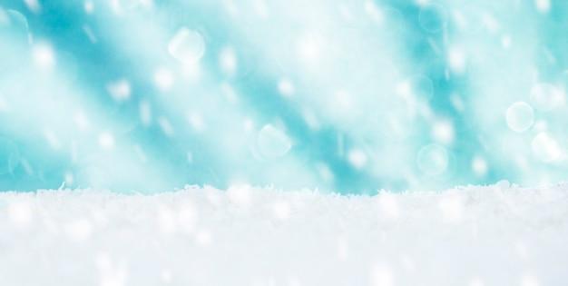 雪とボケのコピースペースが降る美しい明るい焦点ぼけの青い背景