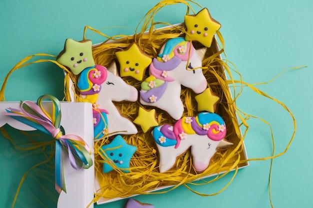 ターコイズブルーの背景のギフトボックスにある休日のための美しく、明るく、フィギュアのジンジャーブレッドクッキー