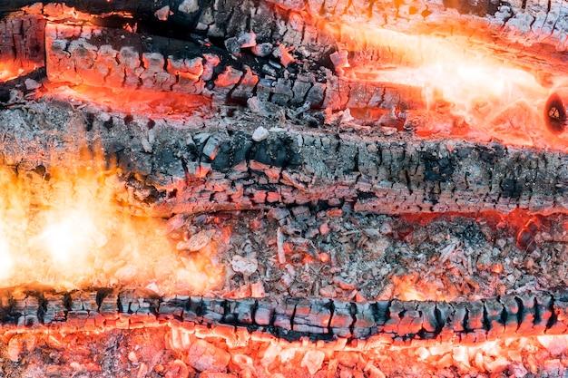 Красивый яркий огонь с раскаленными углями и пеплом.