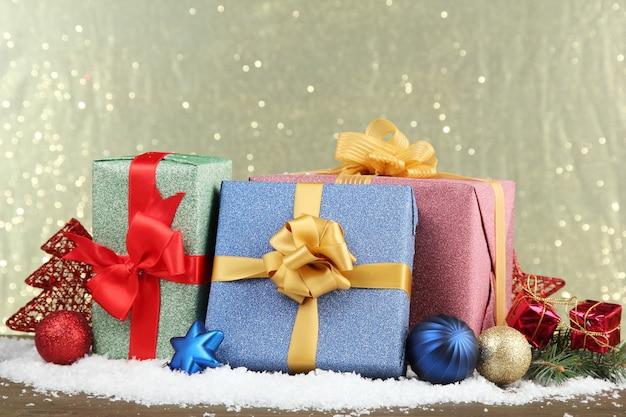 光沢のある背景に、美しい明るい贈り物とクリスマスの装飾
