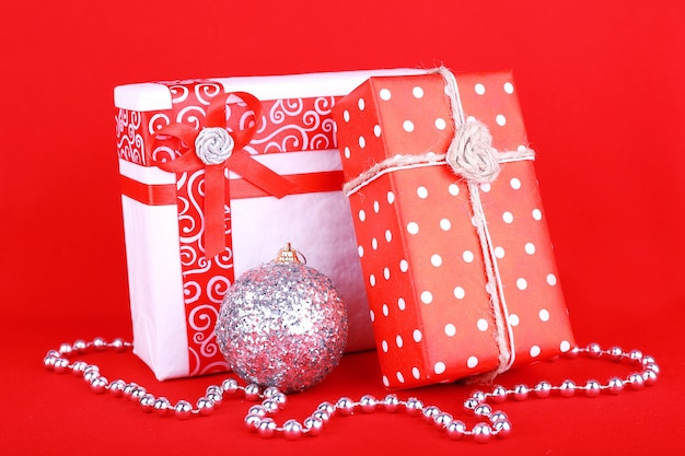 Красивые яркие подарки и новогоднее украшение на красной поверхности