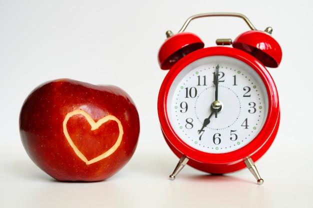 ハート型のカットアウトと赤い丸いクラシックな目覚まし時計付きの美しい明るいジューシーな熟した赤いリンゴ