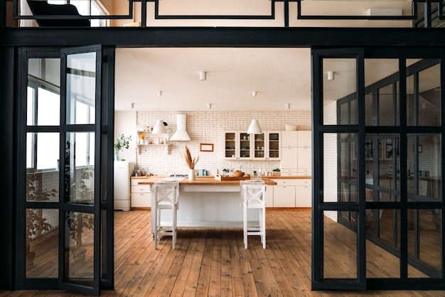 Beautiful bright kitchen with a large table and bar stools and white furniture with wide glass black doors.