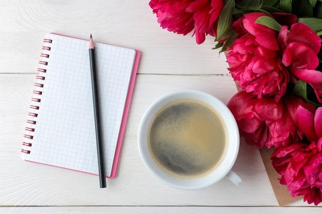 Красивые ярко-розовые цветы пионов и блокнот с чашкой кофе на белом деревянном фоне. вид сверху.