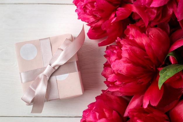 白い木製の背景に美しい明るいピンクの花牡丹とギフトボックス。上面図。