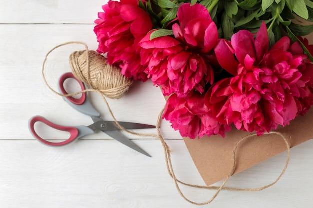 白い木製の背景に美しい明るいピンクの花牡丹と包装紙とはさみ。上面図。ブーケパッキング