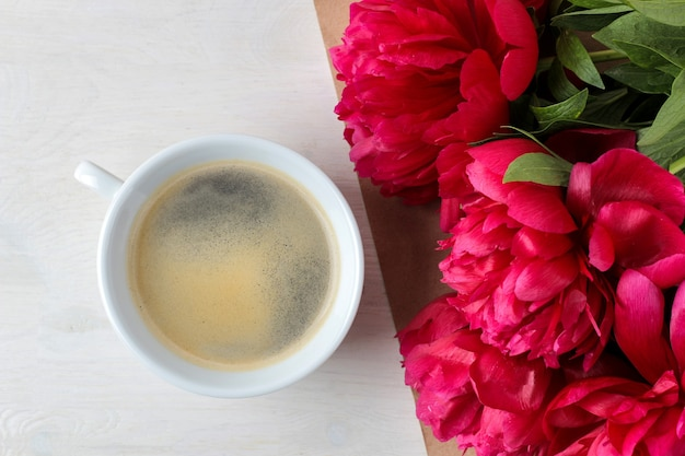 Beautiful bright pink flowers peonies and a cup of coffee on a white wooden background. top view.