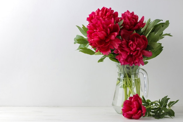 Beautiful bright pink flowers peonies in a jug on a light background. space for text