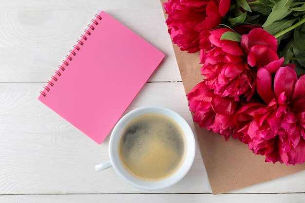 Beautiful bright pink flowers peonies and a notebook with a cup of coffee on a white wooden background. top view.