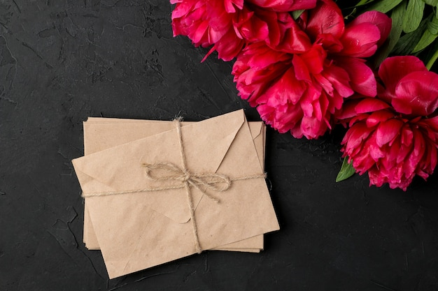 Beautiful bright pink flowers peonies and a stack of envelopes on a black graphite background. top view.