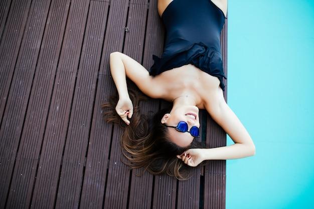Красивая яркая сексуальная веселая женщина лежит на краю бассейна, загорает, наслаждается. идеальное тело и здоровая кожа и волосы, модное бикини, солнцезащитные очки, арбуз. вид сверху