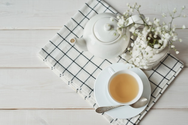 Beautiful bright tea set up. white ceramic tea pots and tea ingredients, on top of the white table.